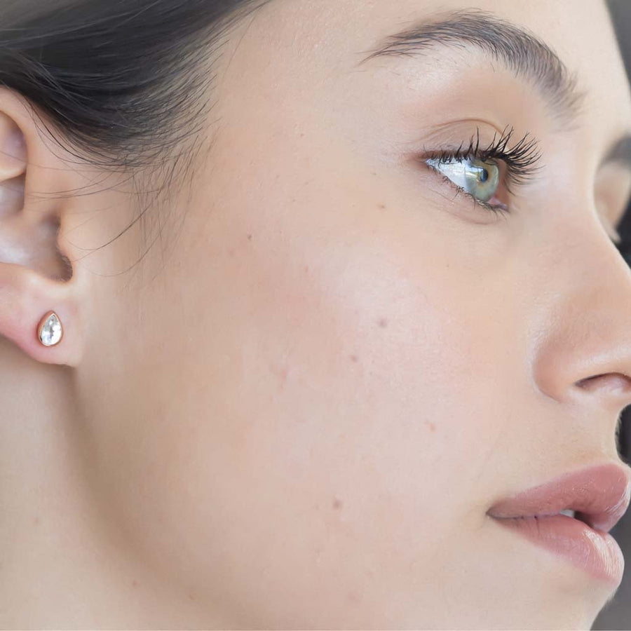 model wearing teardrop stud earrings rose gold clear quartz closeup