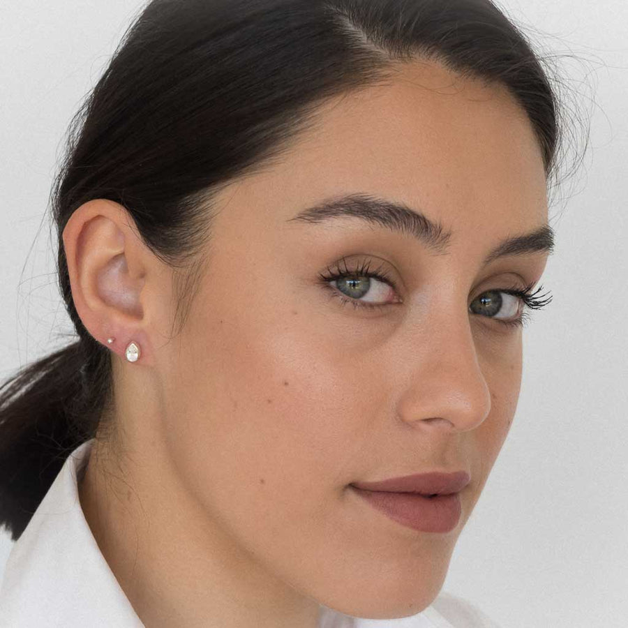 model wearing teardrop stud earrings silver clear quartz