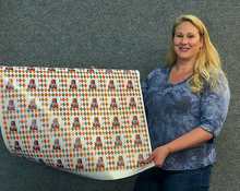 Carrie Weimer holding roll of custom printed gift wrapping paper
