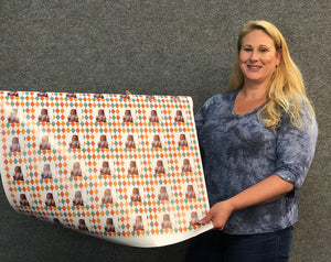 Roll of designer gift wrapping paper held by Carrie Weimer