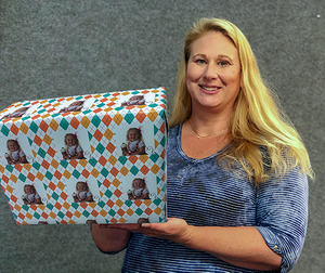 Carrie Weimer holding custom photo gift wrapped package