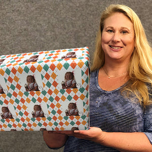 Package wrapped with designer gift wrapping paper held by Carrie Weimer
