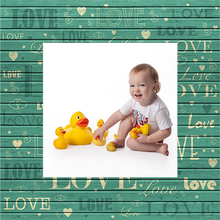 Design with love written many time and photograph of baby playing with rubber ducks