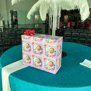 Personalized photo gift wrapped package on table at event