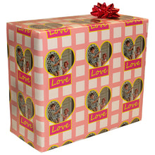 Gift wrapped package with red bow pattern with heart shaped photo and text saying love