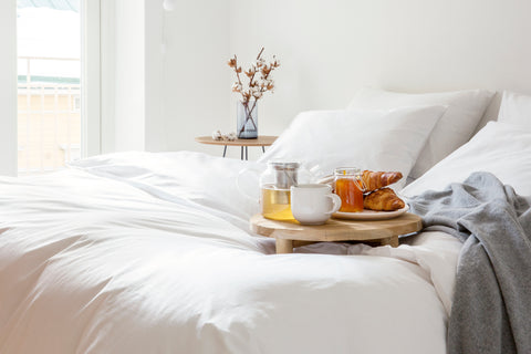 Breakfast on wooden breakfast table with croissant orange juice tea on the wooden table on a beige bed using organic knotte bedsheets with grey mini blanket