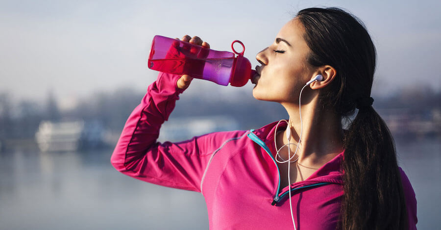 woman in pink drinking water out of pink water bottle in winter