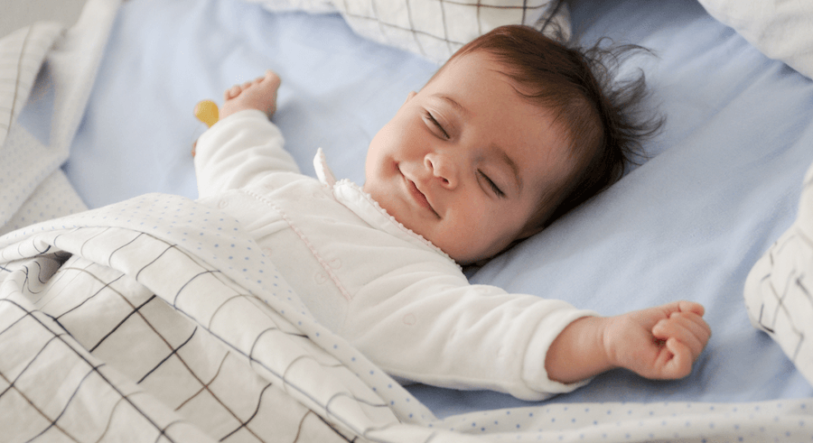 happy baby sleeping peacefully on bed with arms out