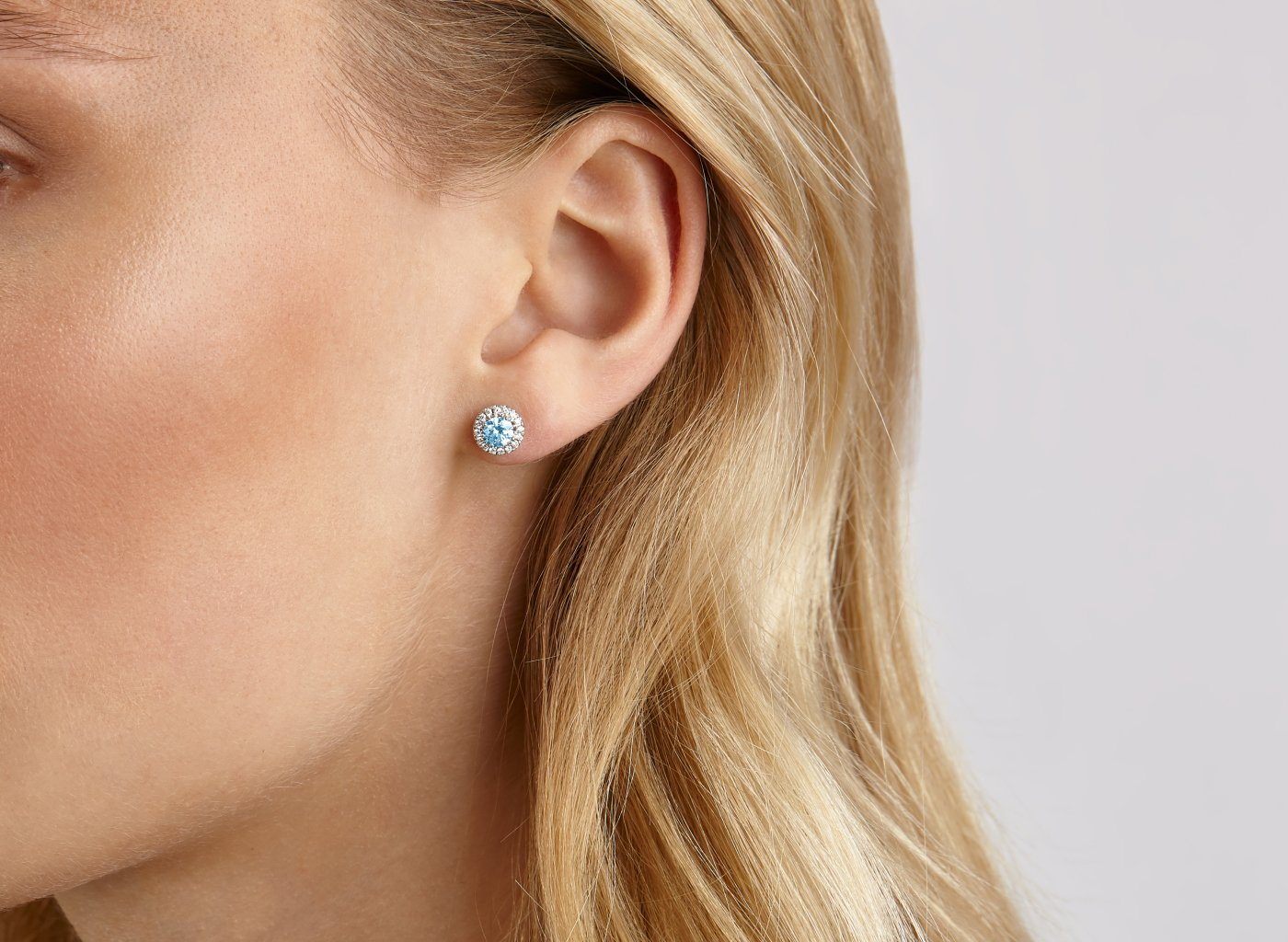 On Model view of Halo 1 carat earrings with blue and white diamonds