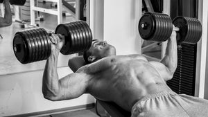 man doing heavy dumbbell bench press