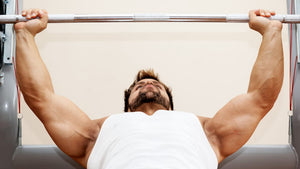 man in white tank top bench press