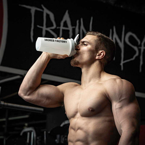 Ripped man drinking disoluted protein powder