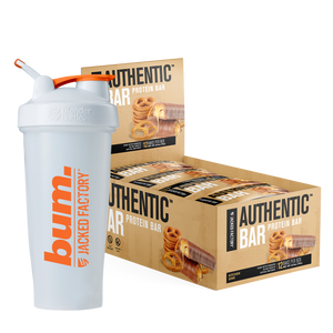 Jacked Factory's 12-pack of Kitchen Sink Authentic Bars in a beige box with pretzel and chocolate image next to a white and orange bum. shaker bottle