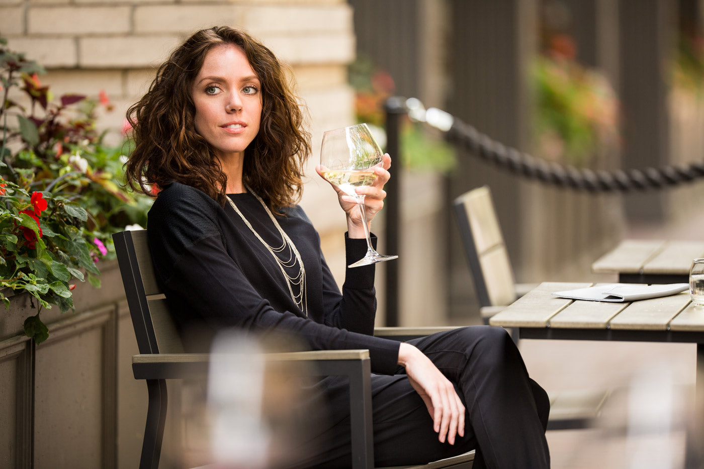 Kathyrn Boren, relaxing with a glass of white wine, wearing MPG clothing