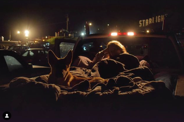 picture of a dog and a its owner cuddled under some blankets at the drive in movie theatre in BC