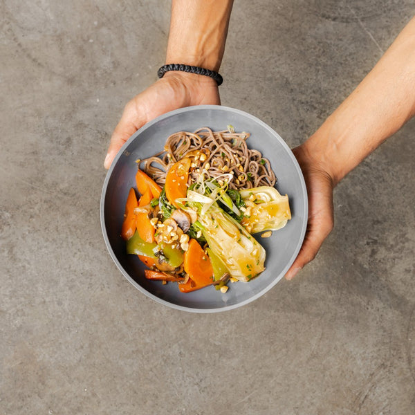 Hands holding bowl of healthy food