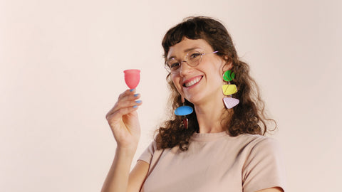 Model holding a Saalt Cup and smiling.