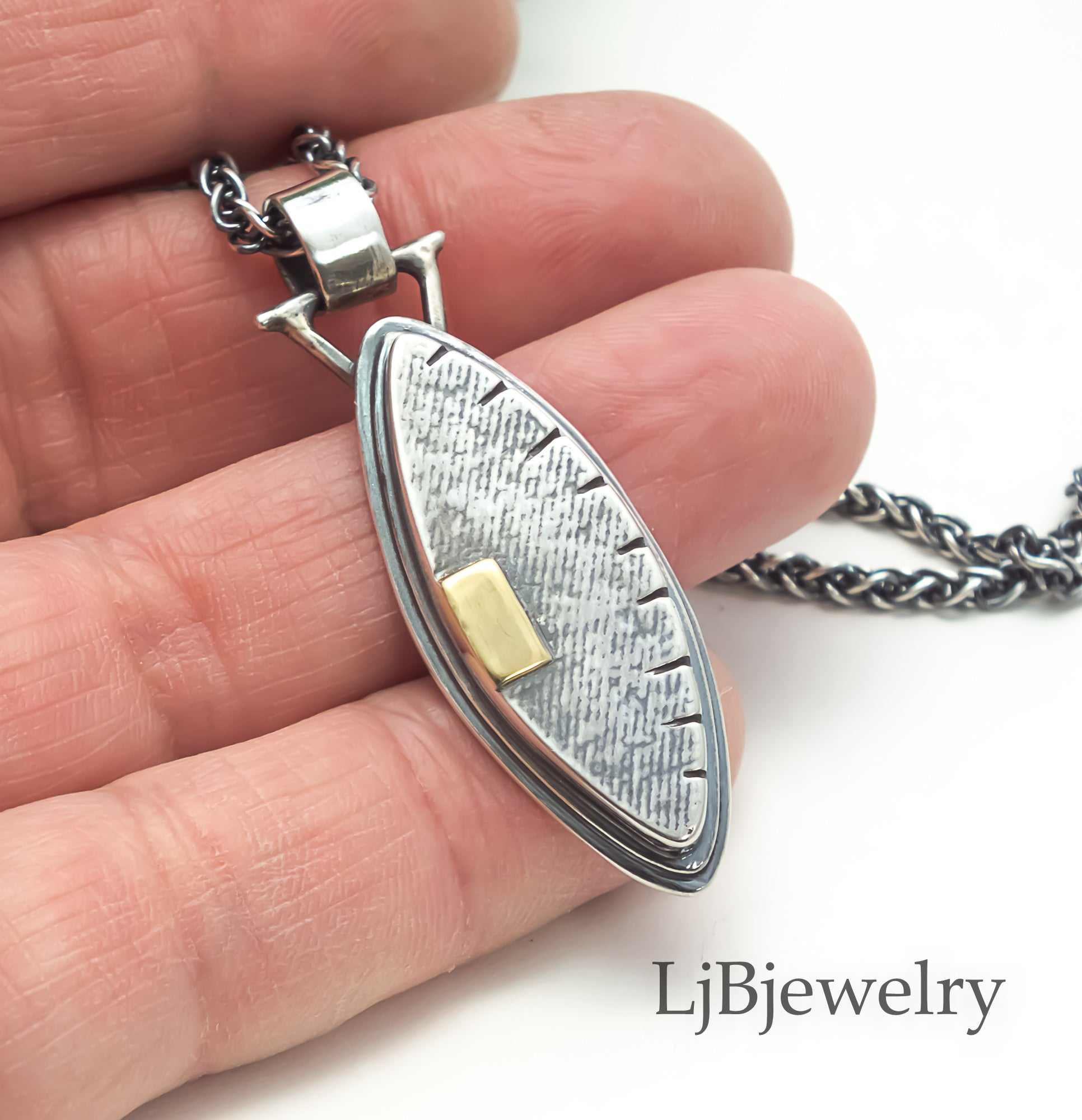 silver and gold hollow form pendant