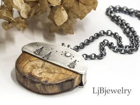 silver pendant with forest and wood slice
