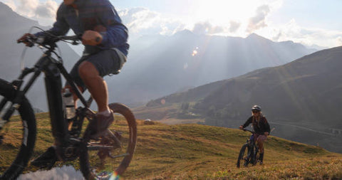 Couple of Mountain e-bikers rides up the hill