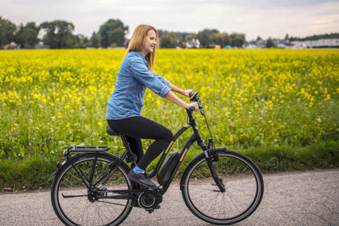 Happy young female riding on her electric bicycle