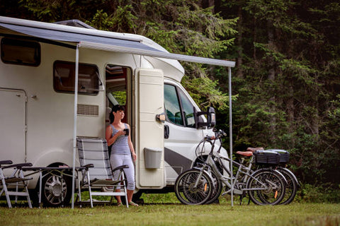 Woman is standing with a mug of coffee near the electric bike and camper RV