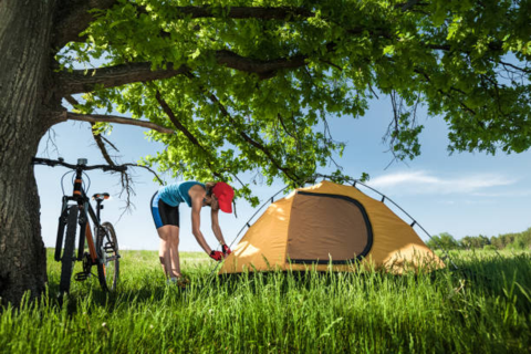 Young Woman enjoys Camping with her Ebike