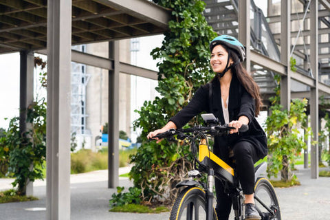 Young woman riding electric bike to work.