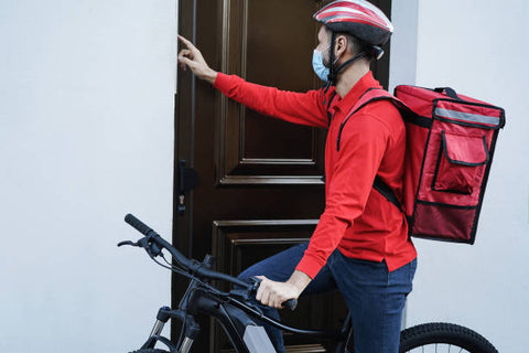delivery man with electric bike ringing the doorbell