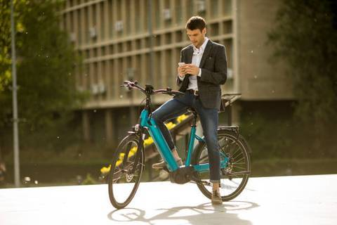 male commuter texting on his electric bike