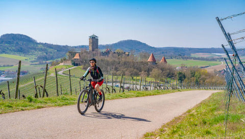 woman on  an Electric mountain bike in vineyard with castle ageless happy senior woman riding her electric mountain bike on sunny spring