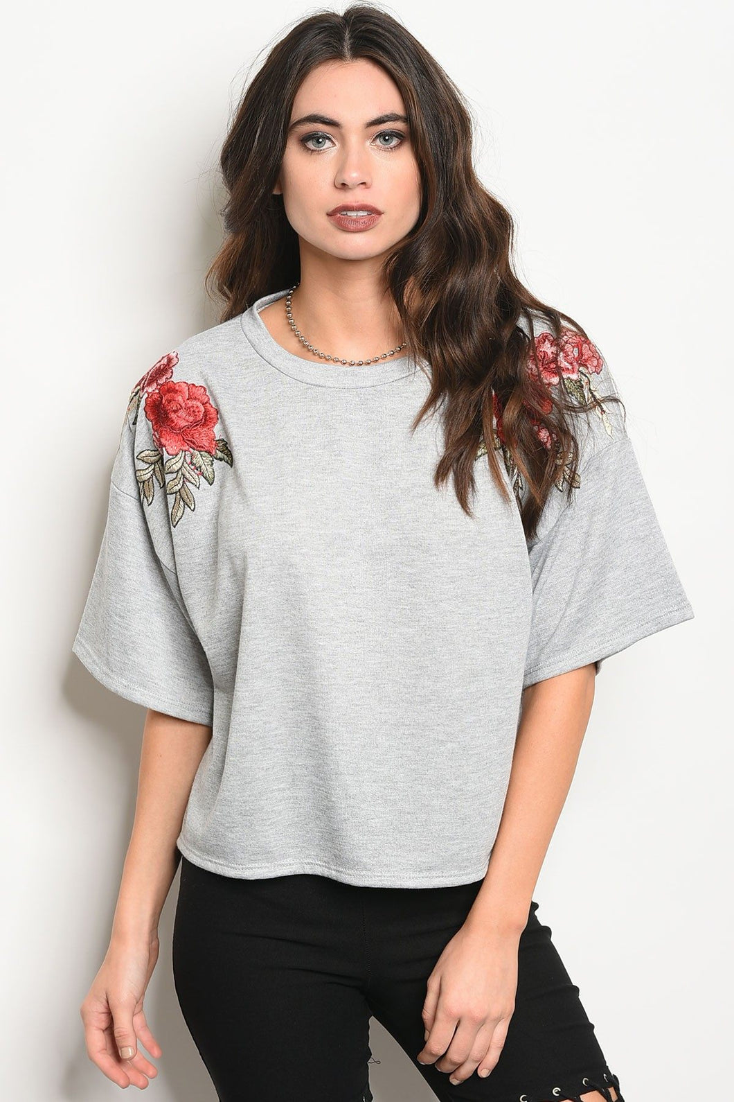 Ladies fashion 3/4 sleeve light weight knit top with a crew neckline and floral patch details