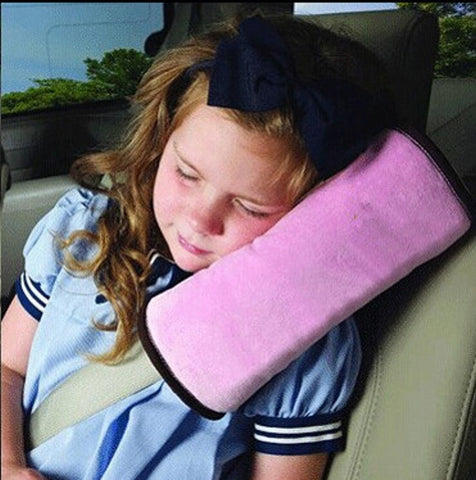 happily taking a nap on the car seat belt pillow