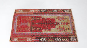Vintage Turkish mini rug in room decor setting, old rug, antique rug, pastel colors, faded colors, Turkish rug, vintage rug, soft rug, Portland, Oregon, rug store, rug shop, local shop