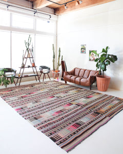 Vintage kilim rug in room decor setting, old rug, antique rug, pastel colors, faded colors, Turkish rug, vintage rug, soft rug, Portland, Oregon, rug store, rug shop, local shop, distressed rug, worn out rug