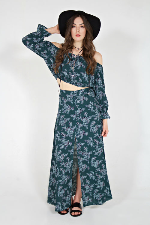 White model in matching teal colored floral long sleeve crop top and maxi skirt set