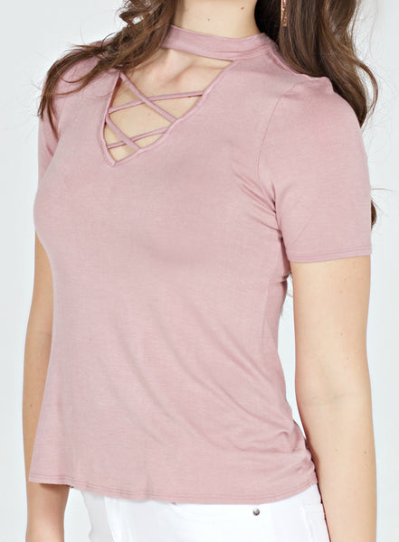 White model in a pink choker crisscross neckline short sleeve top and white jeans