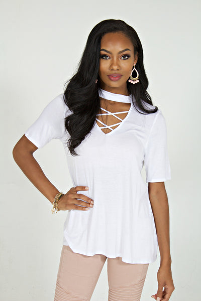 Black model in a white choker crisscross neckline short sleeve top and pink jeans