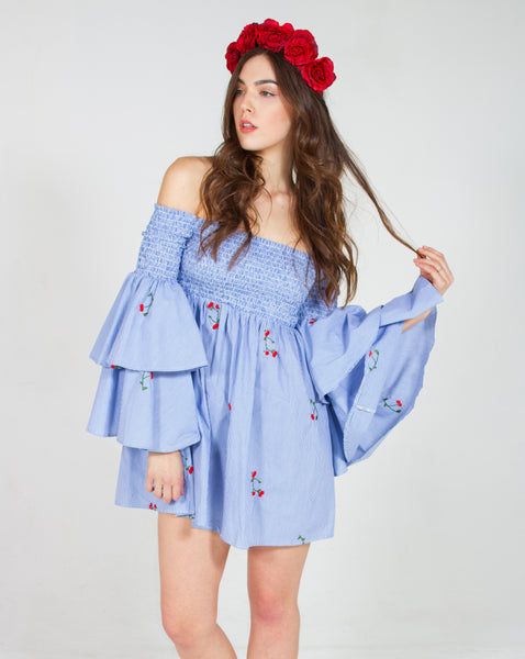 White model wearing a red rose flower crown with a blue off the shoulder dress embroidered with small roses and tiered sleeves