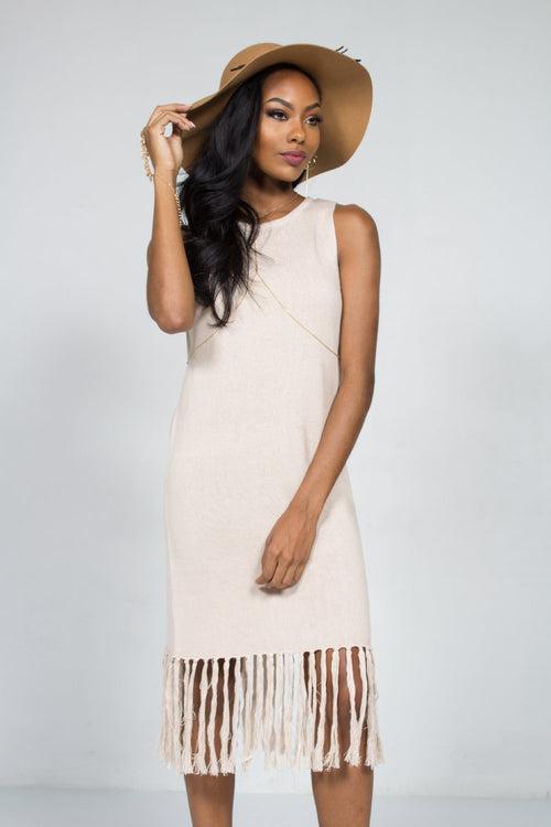 Black model wearing a chunk knit natural color fringe trimmed sweater dress and a floppy brown hat