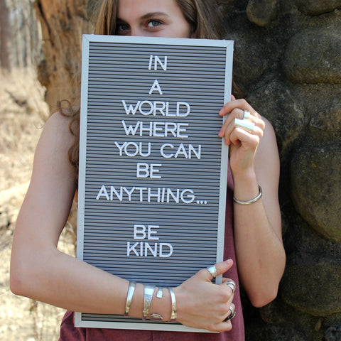 """Photo of a young woman holding a message board that reads """"In a World Where yOU Can be anything, be kind"""" Young woman is wearing Upcycled silverware jewelry"""