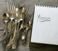 Mission Statement Photo for Laughing Frog Studio showing pile of antique silverware and notepad with handwriting Mission