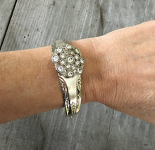 Camelia spoon bracelet with flower shaped rhinestone button shown on model's arm