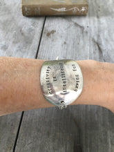 Hand stamped spoon bracelet about creativity shown on model's arm