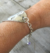 Stamped Spoon Bracelet Love is Love shown on models arm illustrating adjustable sizing chain