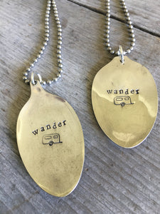 Close up of Stamped Spoon Necklaces Wander with Airstream Trailer