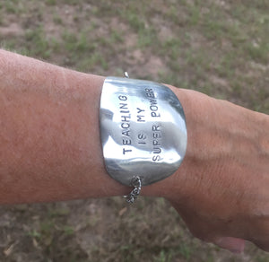 Stamped spoon bracelet with Teaching is my super power shown on wrist
