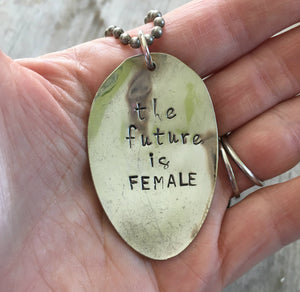 Stamped Spoon Necklace The Future is Female Shown in Hand for Scale