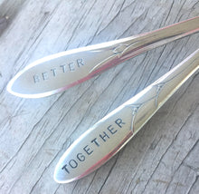 Close up of the handles of Handstamped mismatched set wedding cake forks that read better together