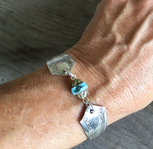 Upcycled silverware bracelet shown on model